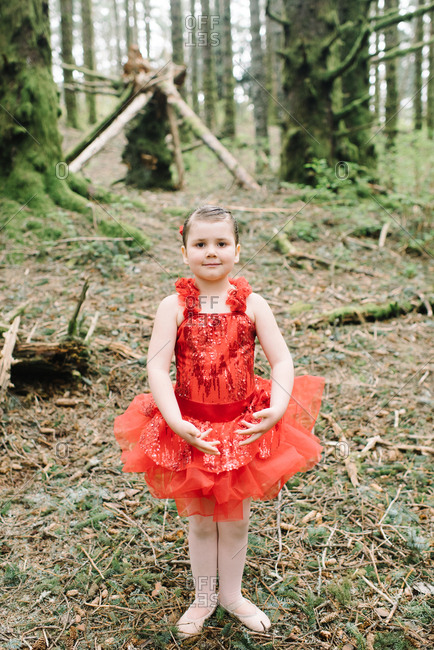 Little girl in a red ballet outfit in the woods
