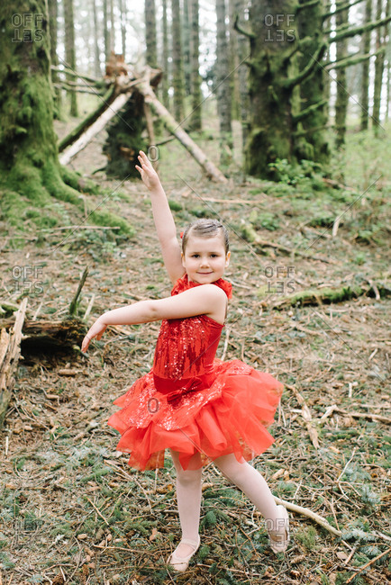 Young girl in a red ballet outfit in the woods