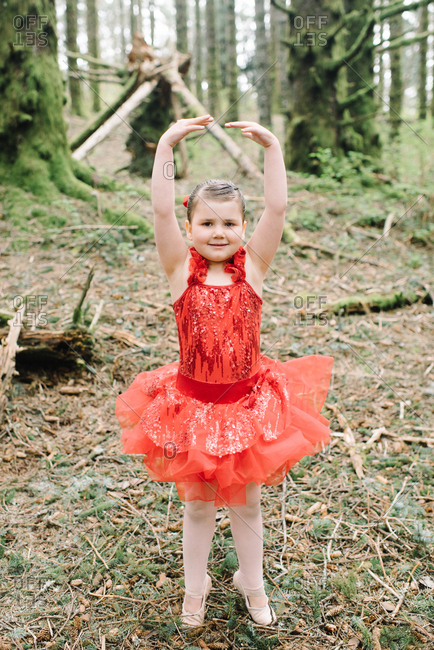 Little girl in a red ballerina outfit in the woods