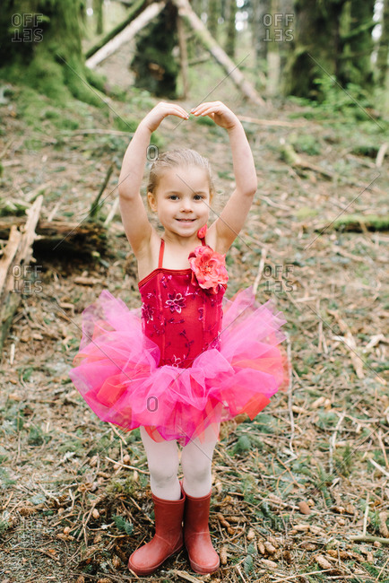 Young girl in a pink ballet outfit in the woods