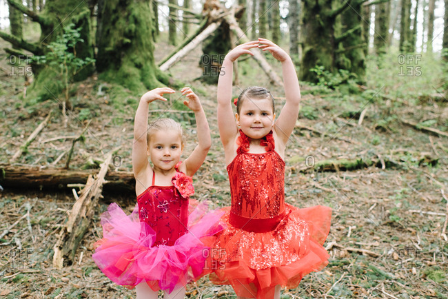 Two little girl in a red ballerina outfit in the woods