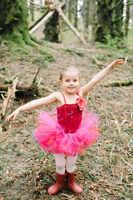 Little girl in a pink ballet outfit in the woods