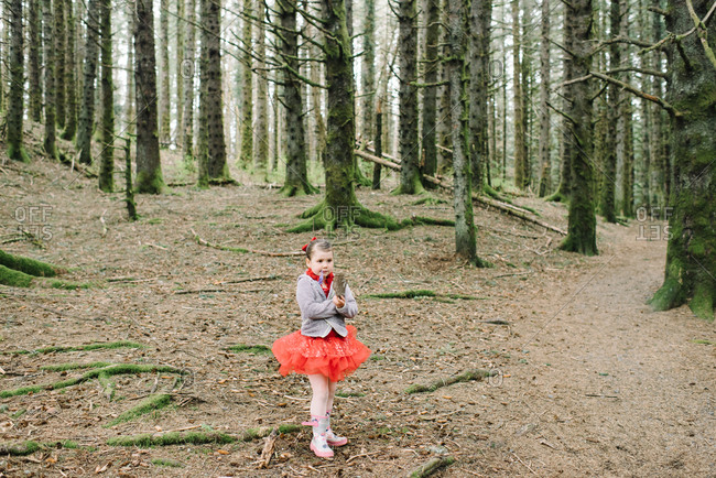 Young girl in a red ballet outfit walking in the woods