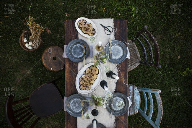 Aerial view of a garden party in Italy. Dining table with food platters, linen napkins, glass of wine and candlesticks