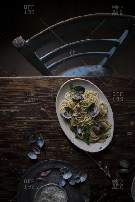 Overhead view of a wooden table with an oval dish of spaghetti with clams