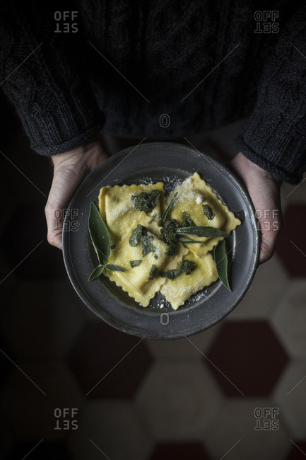 Overhead view of a person holding a dish of homemade ravioli seasoned with butter, sage and Parmesan cheese