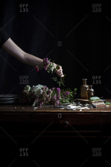 Hand of a woman laying a bunch of flowers on a table, on a dark background