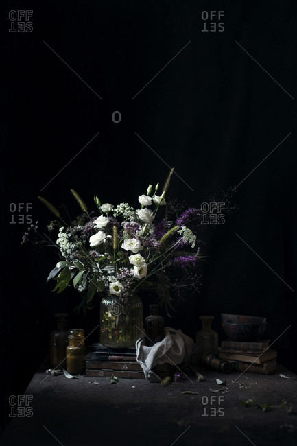 Flowers bouquet on a table with vintage props on a dark background