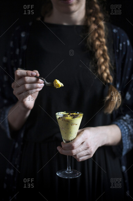 Woman with braid on a dark background eating lemon tiramisu from a glass with a spoon