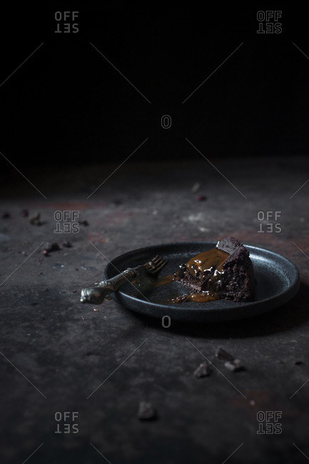 A slice of chocolate & caramel mud cake on a plate on a dark background