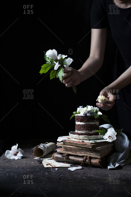 A woman decorating a layer mini cake with some hibiscus flowers on a dark background with vintage props