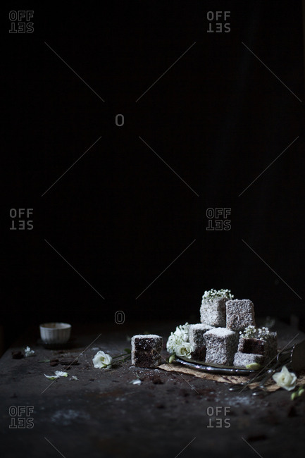 Lamingtons dipped in chocolate, rolled in coconut flakes on a rusty table on a dark background
