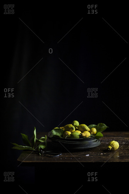 Freshly picked lemons with leaves on a wooden table, on a dark background