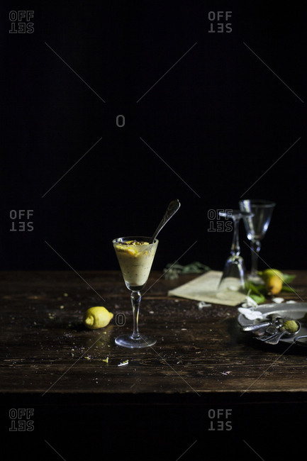 Glass of lemon tiramisu with spoon on a wooden rustic table on a dark background
