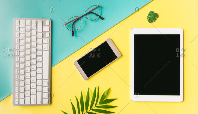 Smartphone, tablet computer, keyboard, and glasses, on a yellow background