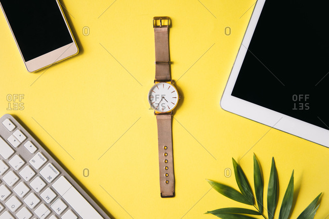 Golden watch, smartphone, and tablet with keyboard on a yellow background