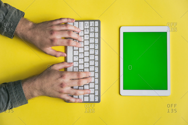Top view of male hands writing on a keyboard on colorful background