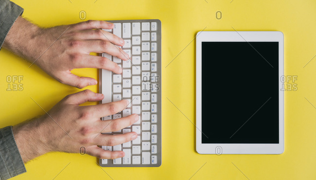 Top view of male hands writing on a keyboard on yellow background