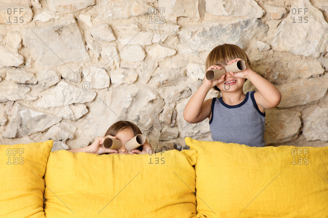 Two kids behind a yellow sofa looking through toilet paper rolls