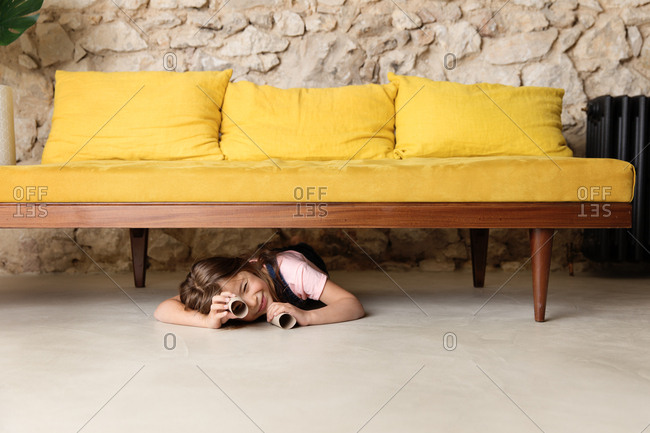 Girl under a yellow sofa looking through toilet paper rolls