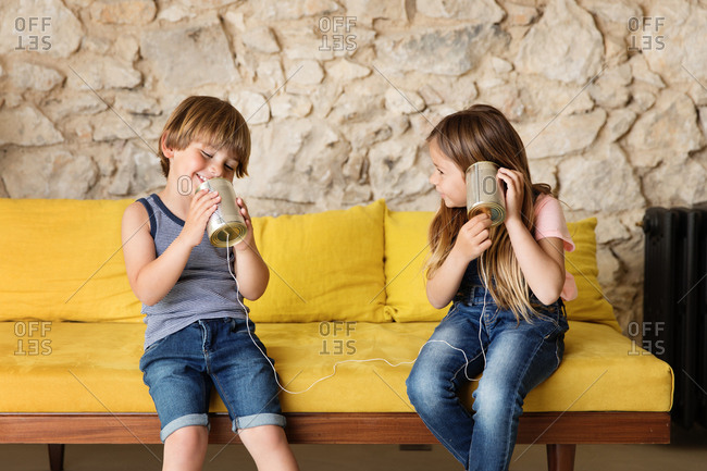 Two kids sitting on yellow sofa playing with tin can telephone