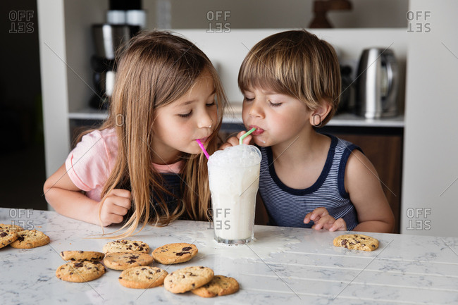 Two kids blowing bubbles in a glass of milk with straws