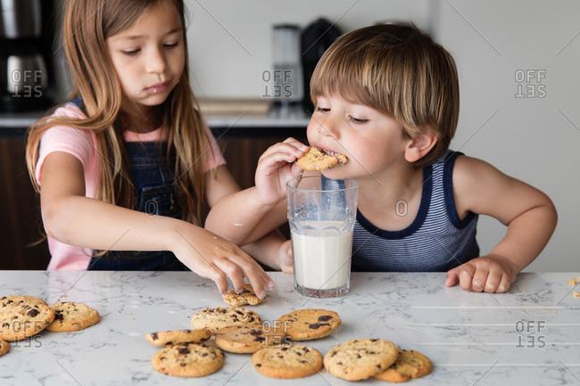 Siblings eating cookies and milk