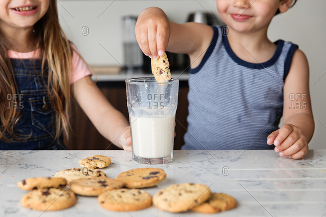 Boy dipping cookie into milk