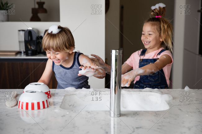 Kids throwing suds while washing dishes