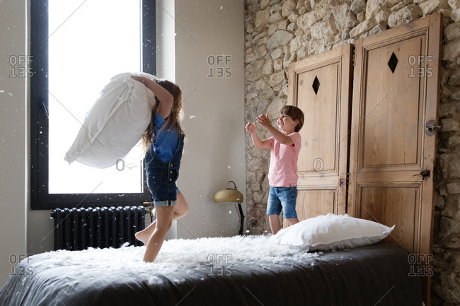Two kids having a pillow fight on a bed