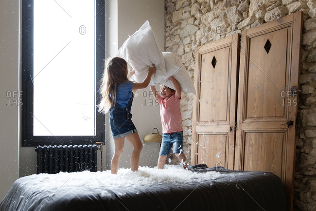 Siblings kids having a pillow fight on a bed