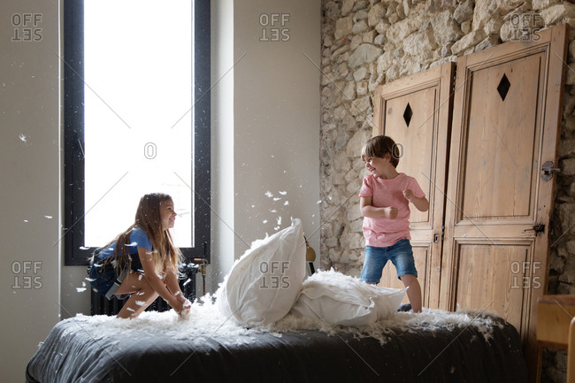 Two kids having a pillow fight