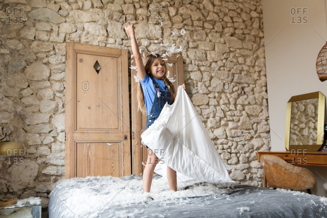 Little girl throwing feathers from a pillow into the air