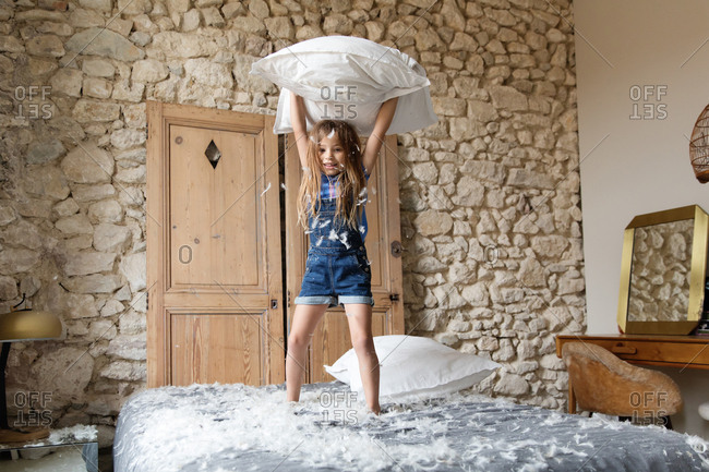 Little girl throwing a pillow into the air