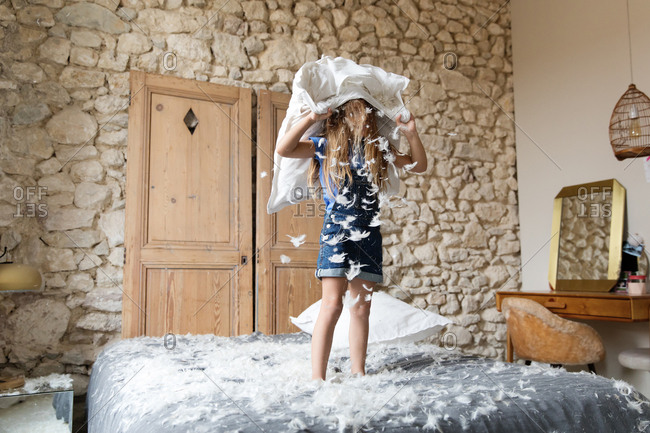 Little girl making a mess with a feather pillow