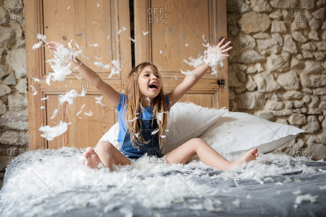 Little girl throwing stuffing from a feather pillow