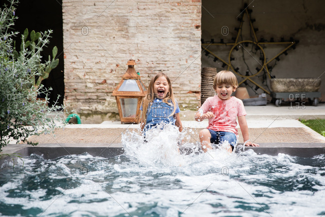Two siblings splashing on the edge of a pool