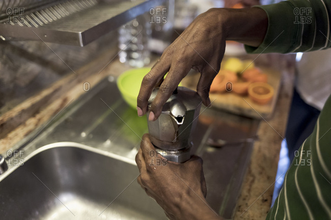 Close up of a Brazilian man preparing coffee at home