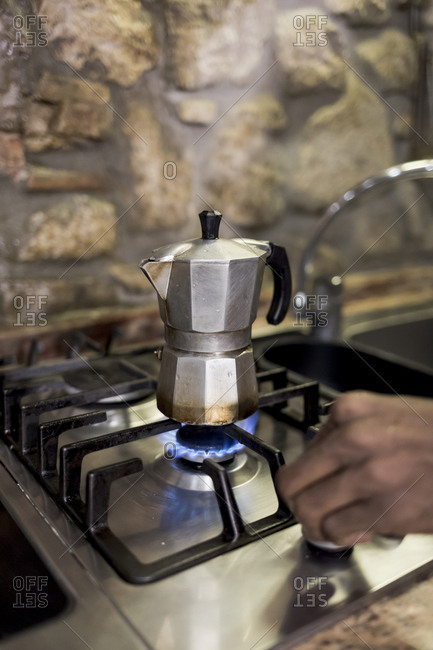 Brazilian man turning gas stove on to make coffee at home