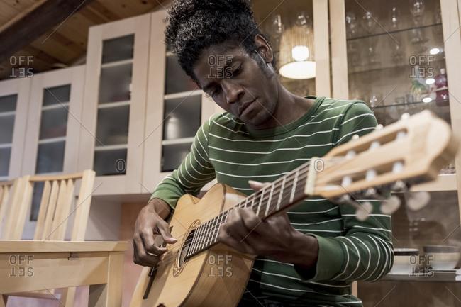 Brazilian man playing guitar at home