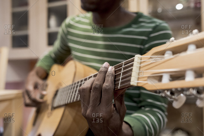 Close up of a Brazilian man playing guitar at home