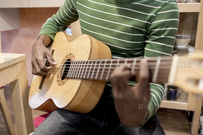 Close up of a Brazilian man playing an acoustic guitar at home