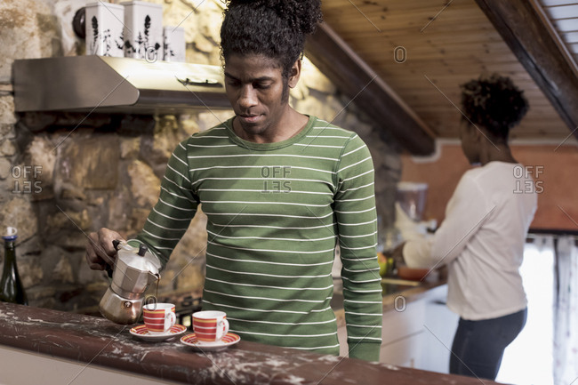 Brazilian man pouring coffee at home with woman in background