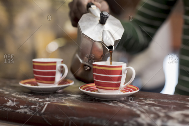 Close up of a Brazilian man pouring two cups of coffee at home