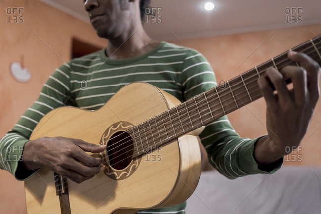 A Brazilian man playing an acoustic guitar at home