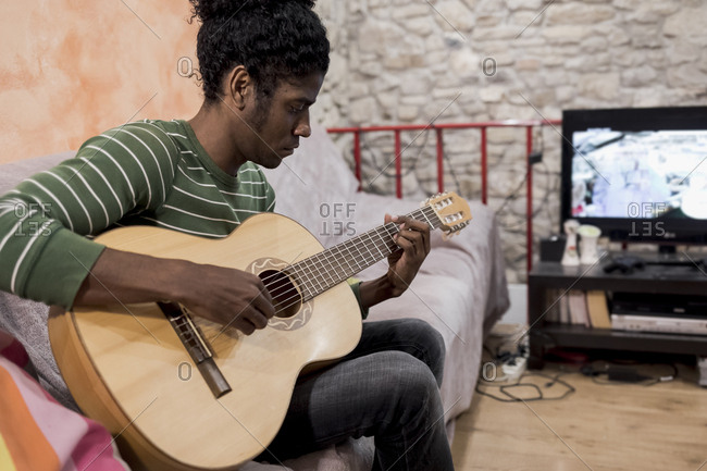 Brazilian man sitting on sofa playing an acoustic guitar