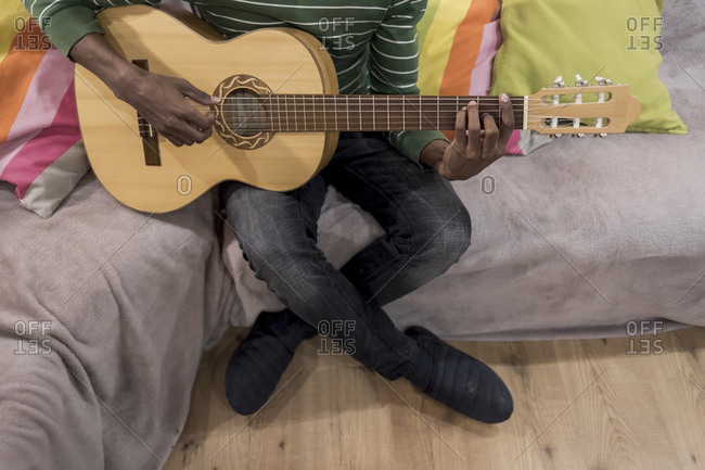 A Brazilian man sitting on sofa playing an acoustic guitar
