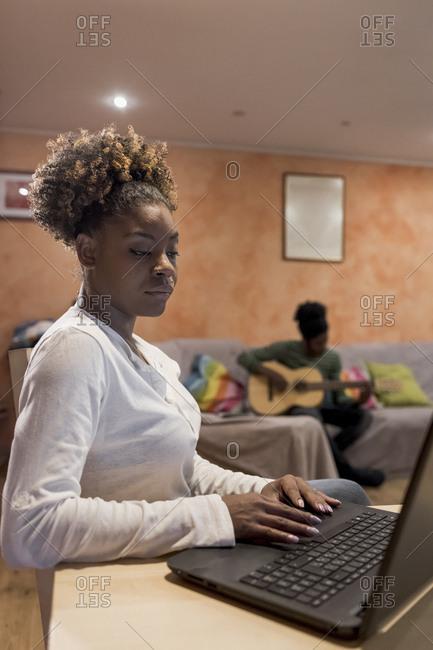 Brazilian woman using laptop at home