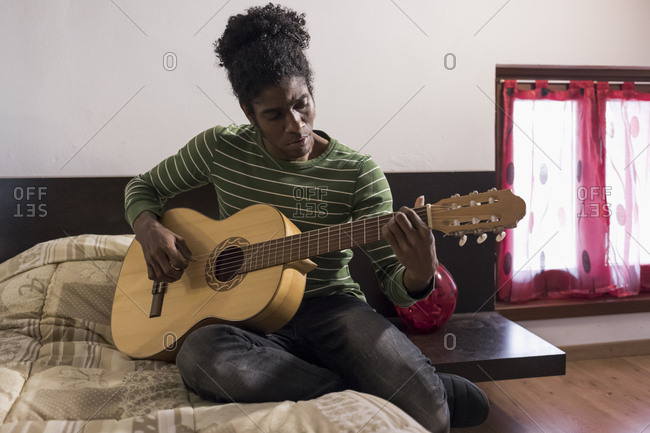 Man sitting on bed playing guitar at home