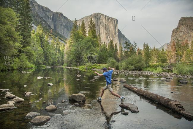 Teenage boy leaping across rocks in lake, Yosemite National Park, California, USA